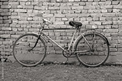 Obraz old bicycle leaning against a wall