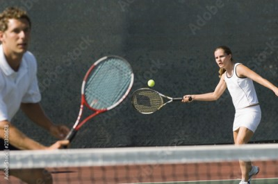 Obraz mixed doubles player hitting tennis ball partner standing near net