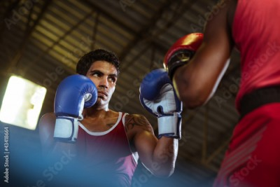 Fototapeta Two male athletes fight in boxing ring