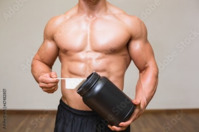 Fototapeta Body builder holding a scoop of protein mix in gym