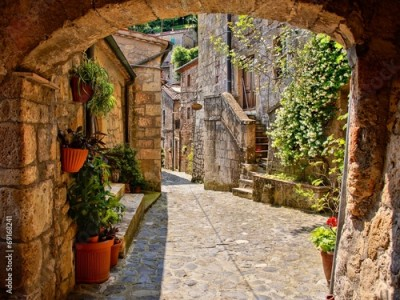 Fototapeta Arched cobblestone street in a Tuscan village, Italy