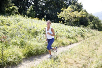 Fototapeta Athletic woman running in countryside