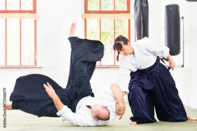 Obraz na płótnie Man and woman fighting at Aikido martial arts school
