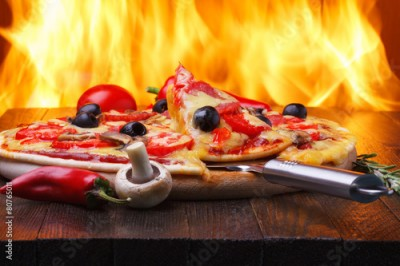 Fototapeta Pizza on wooden table with real oven fire on backgroud