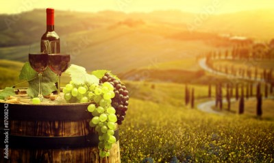 Obraz Red wine with barrel on vineyard in green Tuscany, Italy