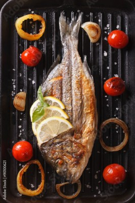 Fototapeta dorado fish with vegetables closeup on the grill. Vertical top view