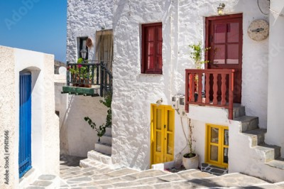 Fototapeta Scenic view of colorful street in traditional Greek cycladic vil