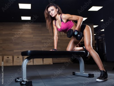 Fototapeta Fitness young sexy girl in the gym doing exercises with dumbbell