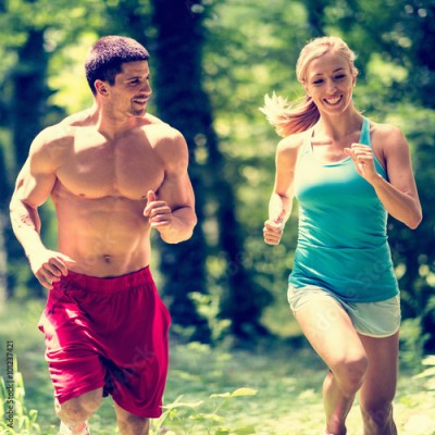 Fototapeta Cheerful couple jogging in the park