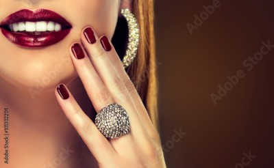 Fototapeta Beautiful girl showing black manicure nails . makeup and cosmetics , beautiful smile with white teeth. Jewelry ,ring and earrings