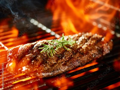 Fototapeta flat iron steak cooking on flaming grill with rosemary garnish