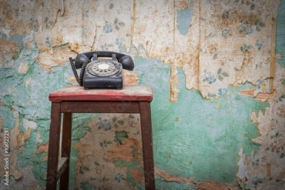 Fototapeta Old vintage phone on a chair stool in front of grunge wallpaper background