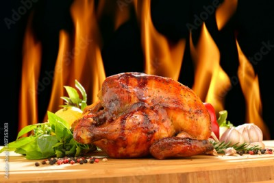 Fototapeta Roast chicken and various vegetables on a chopping wood