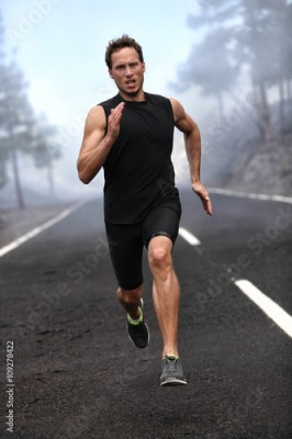 Fototapeta Running runner man sprinting workout on mountain road. Jogging male fitness model working out training for marathon on forest road in amazing nature landscape.