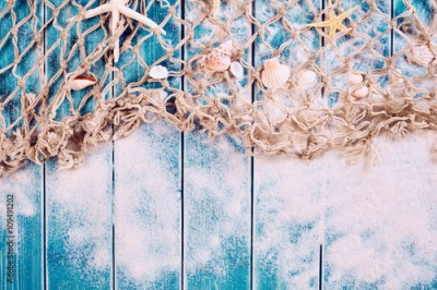 Fototapeta Wooden blue background with sand, net and shells
