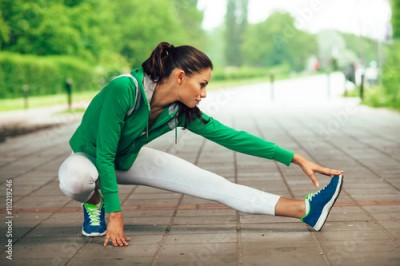 Fototapeta Young fitness woman runner stretching legs before run