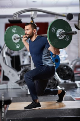 Fototapeta Man doing squats with barbell on neck