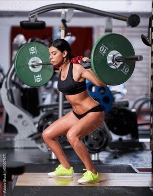 Fototapeta Woman doing squats with barbell on neck