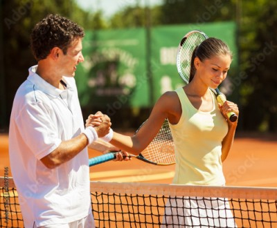 Obraz Young couple finish a tennis match.Shaking hands.