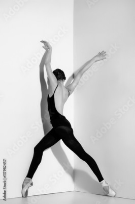 Fototapeta Ballerina in black outfit posing on pointe shoes, studio background.