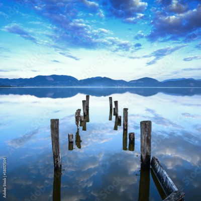 Fototapeta Wooden pier or jetty remains on a lake sunset. Tuscany, Italy