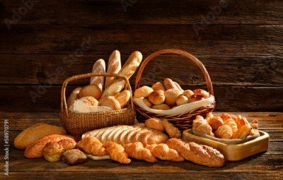 Obraz na płótnie Variety of bread in wicker basket on old wooden background.