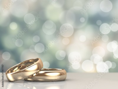 Fototapeta A pair of gold wedding rings with bokeh background