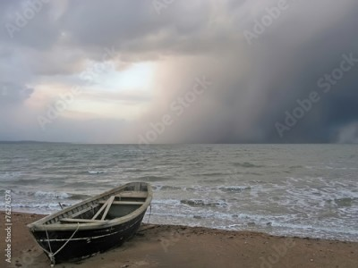 Obraz na Plexi Lonely boat on the shore of a stormy sea