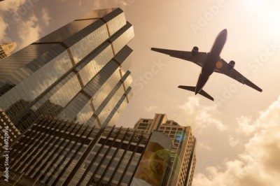 Fototapeta Airplane in golden sky with modern buildings