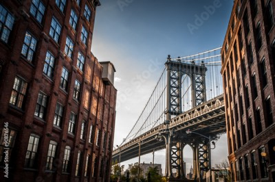 Fototapeta Manhattan bridge seen from a narrow alley enclosed by two brick buildings on a sunny day in summer