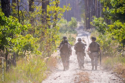 Fototapeta Group of armed soldiers on the road in forest