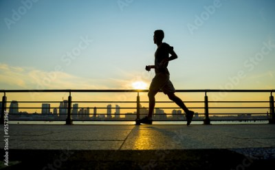 Fototapeta Silhouette of jogger running at sunset in front of the city skyline