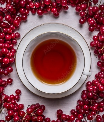 Plakat white cup of tea on a saucer on a white wooden background frame of red berries Viburnum  close up top view