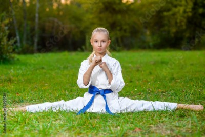 Obraz na płótnie girl in white kimono during training karate exercises at summer