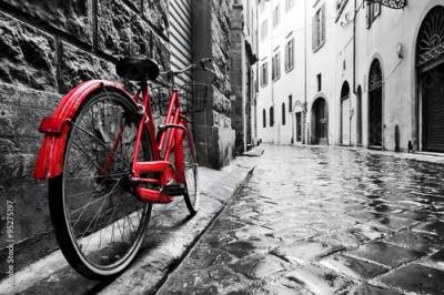 Obraz Retro vintage red bike on cobblestone street in the old town. Color in black and white