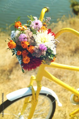 Obraz Beautiful yellow bicycle with bouquet of flowers in basket, outdoors