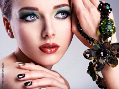 Fototapeta Beautiful woman face with fashion green make-up and jewelry on h