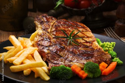 Fototapeta Grilled beef steak served with French fries and vegetables on a