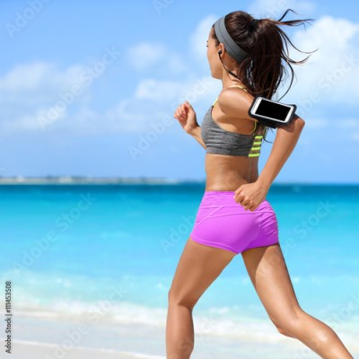 Fototapeta Fit woman running working out cardio exercise on summer tropical beach. Unrecognizable athlete runner jogging intense wearing phone armband holder for music motivation listening on smartphone app.
