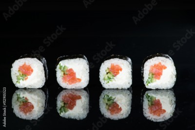 Obraz na płótnie close-up of sushi with salmon and cucumber on a dark background