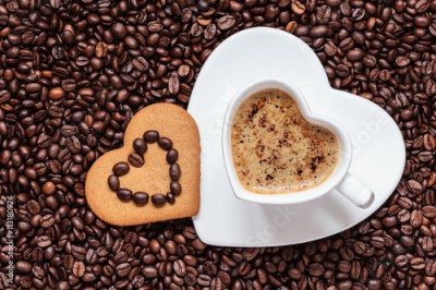 Fototapeta Heart shaped cup and cookie on coffee beans background