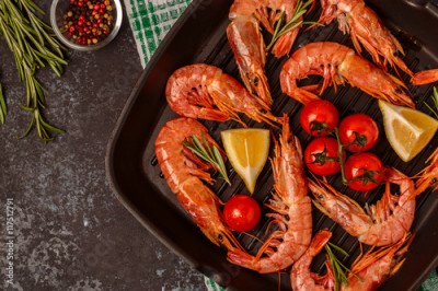Fototapeta Grilled shrimps with lemon and rosemary on frying pan.