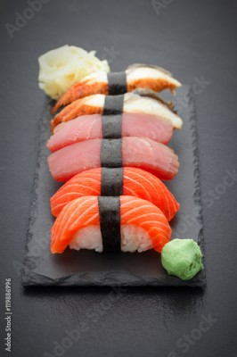 Obraz na płótnie Sushi nigiri set on a stone plate over black background